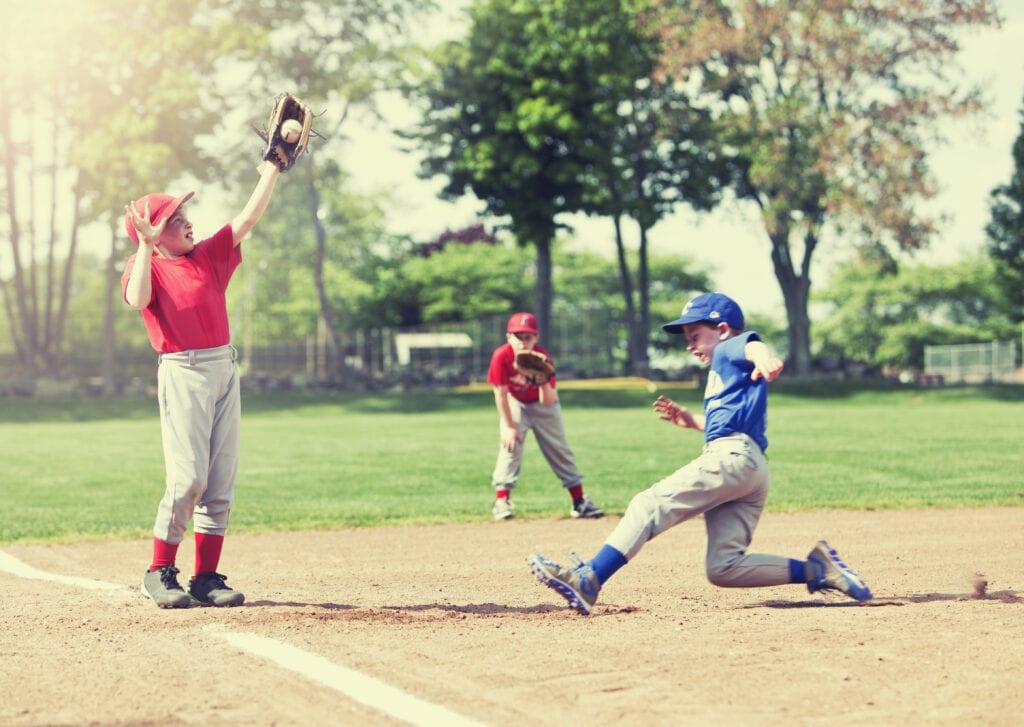 boy sliding into base during baseball game sports injuries