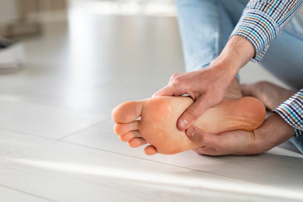 man massaging foot with plantar fasciitis