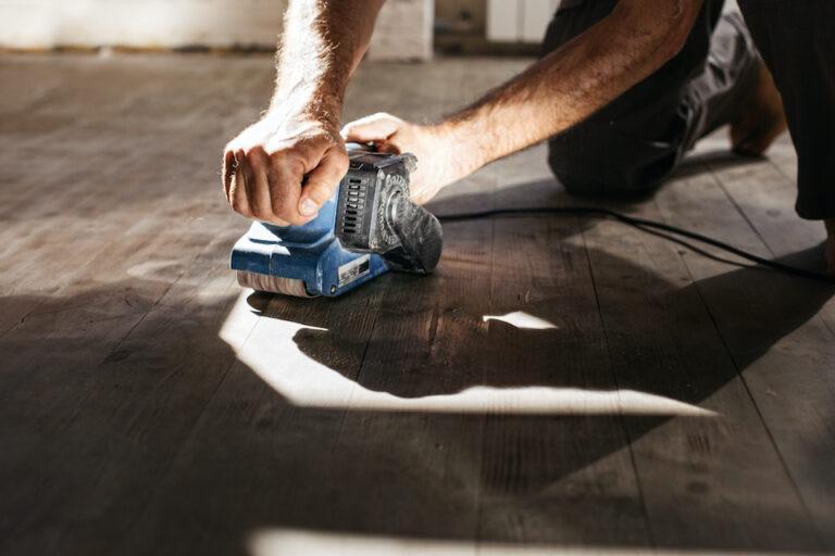 Men's hands make repairs at home. Grinding machine with a wooden floor; oak floor restoration