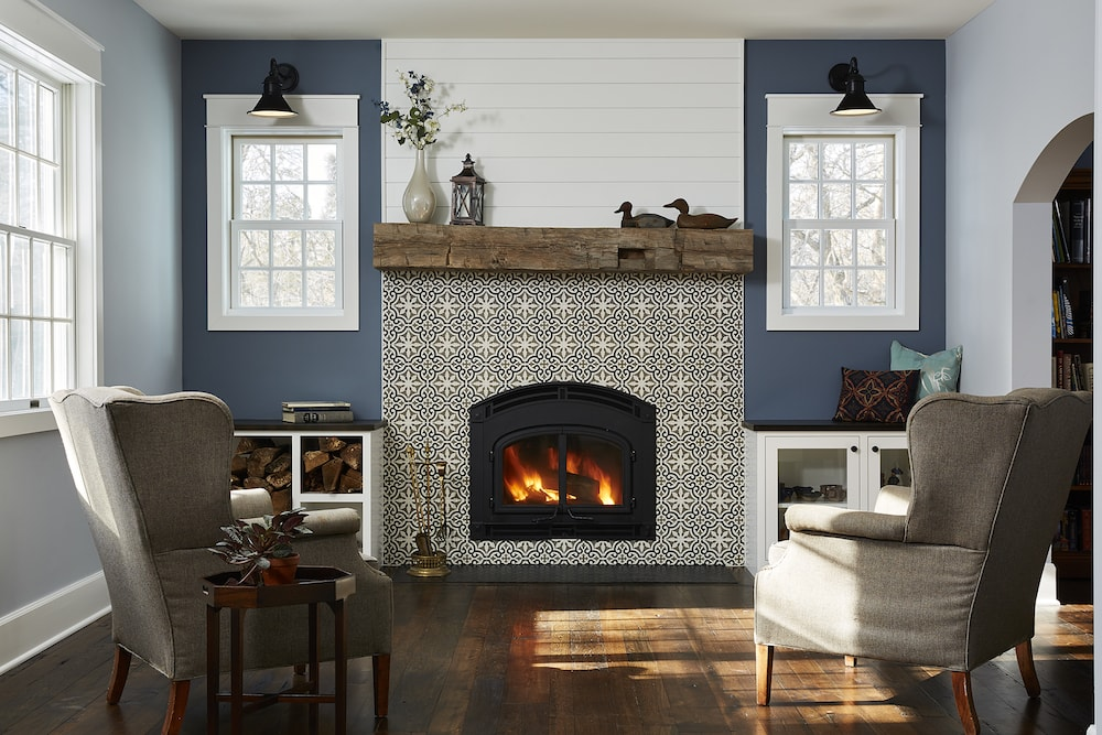 Reclaimed wood mantel above warm fireplace
