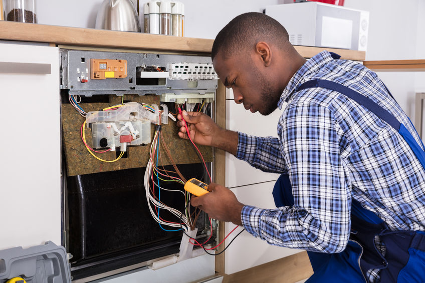Young Male African Technician Fixing Dishwasher With Digital Multimeter In Kitchen