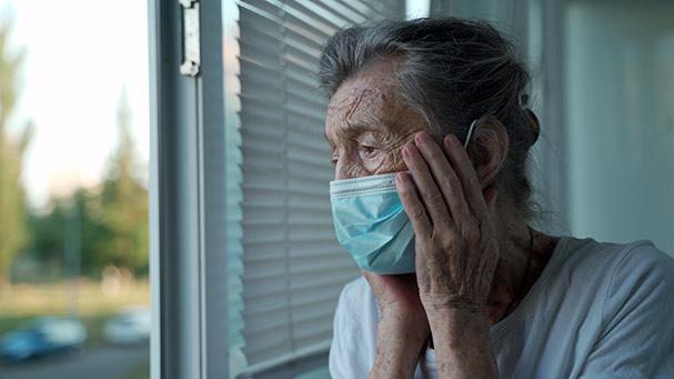 Sad elderly female looking out window of nursing home.