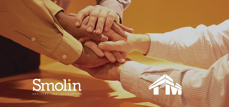 a group of businesspeople holding hands in support. Logos over the picture for Smolin Advisory, Tax, and Accounting and for T & M