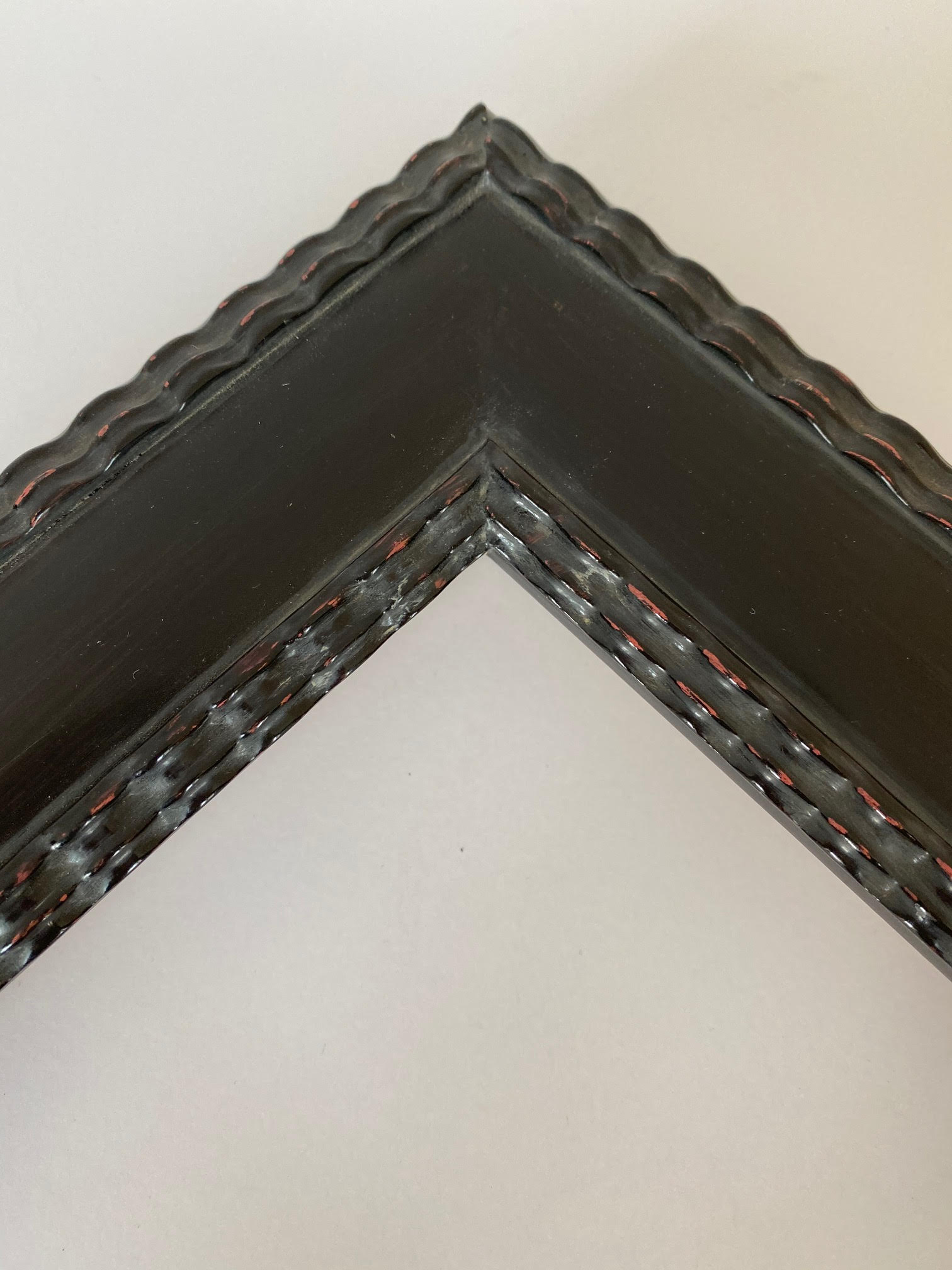 Contemporary Influenced frame profile, ebonized black lacquer finish, rippled moulding on lip and exterior edge.  Artifact Services custom framing. Artmill Group