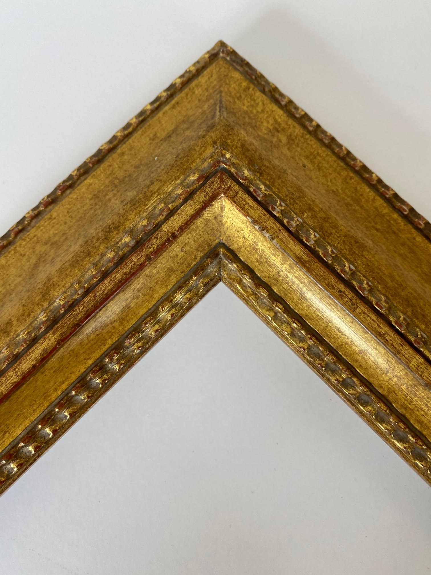 2.5 inch 22k gold leaf Dutch frame with light red rub and brown washed patina