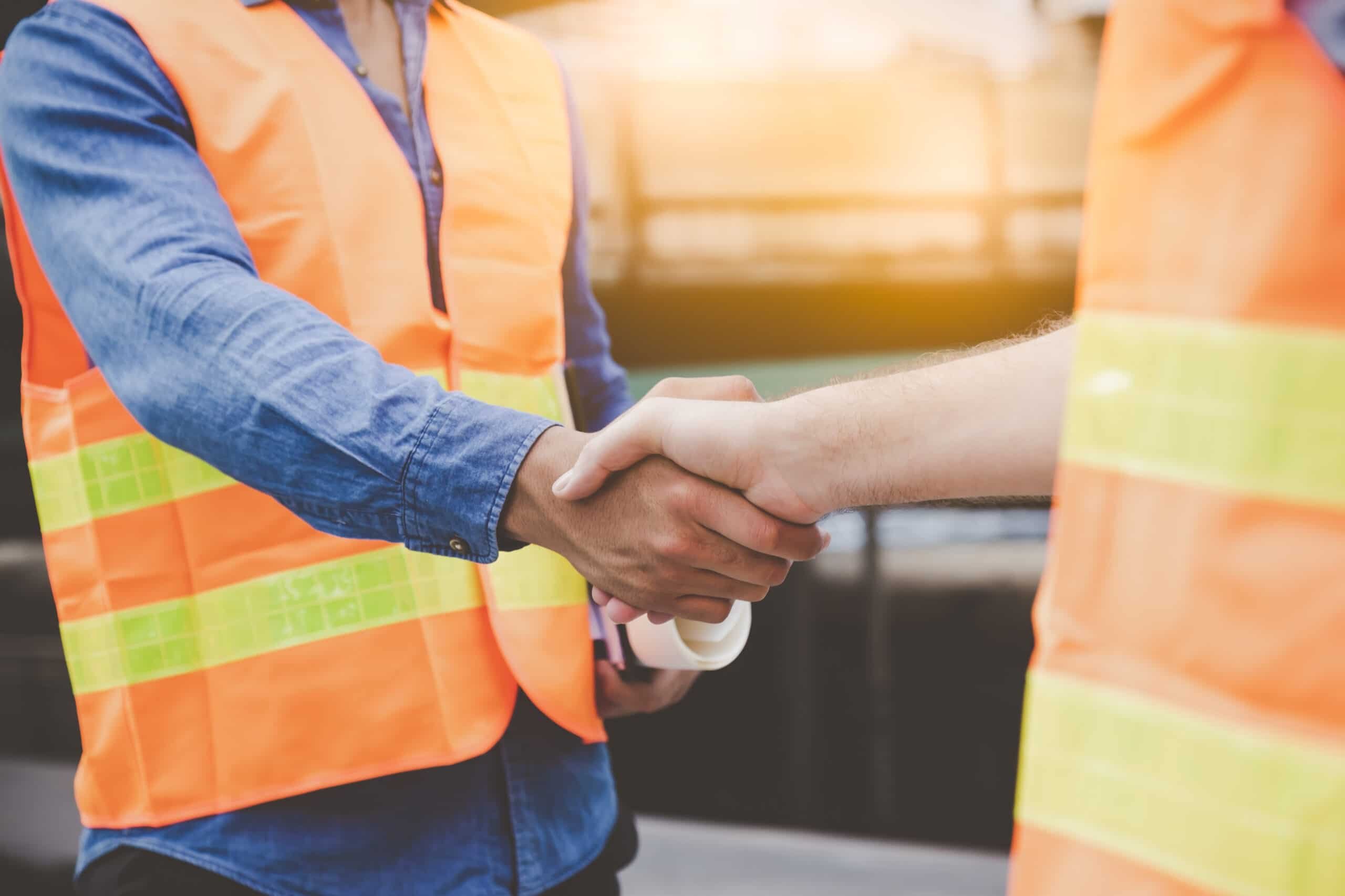 Engineer men making handshake in construction site. Employee or worker shake hands to employer man for greeting, dealing, teamwork, collaboration some project or business. They are good team