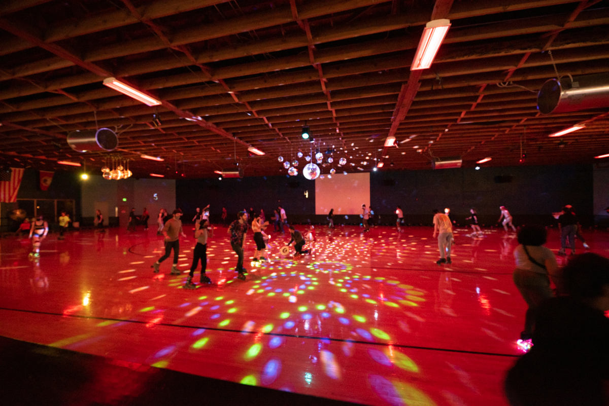 hardwood floor lit with multicolor disco lights and skaters skating