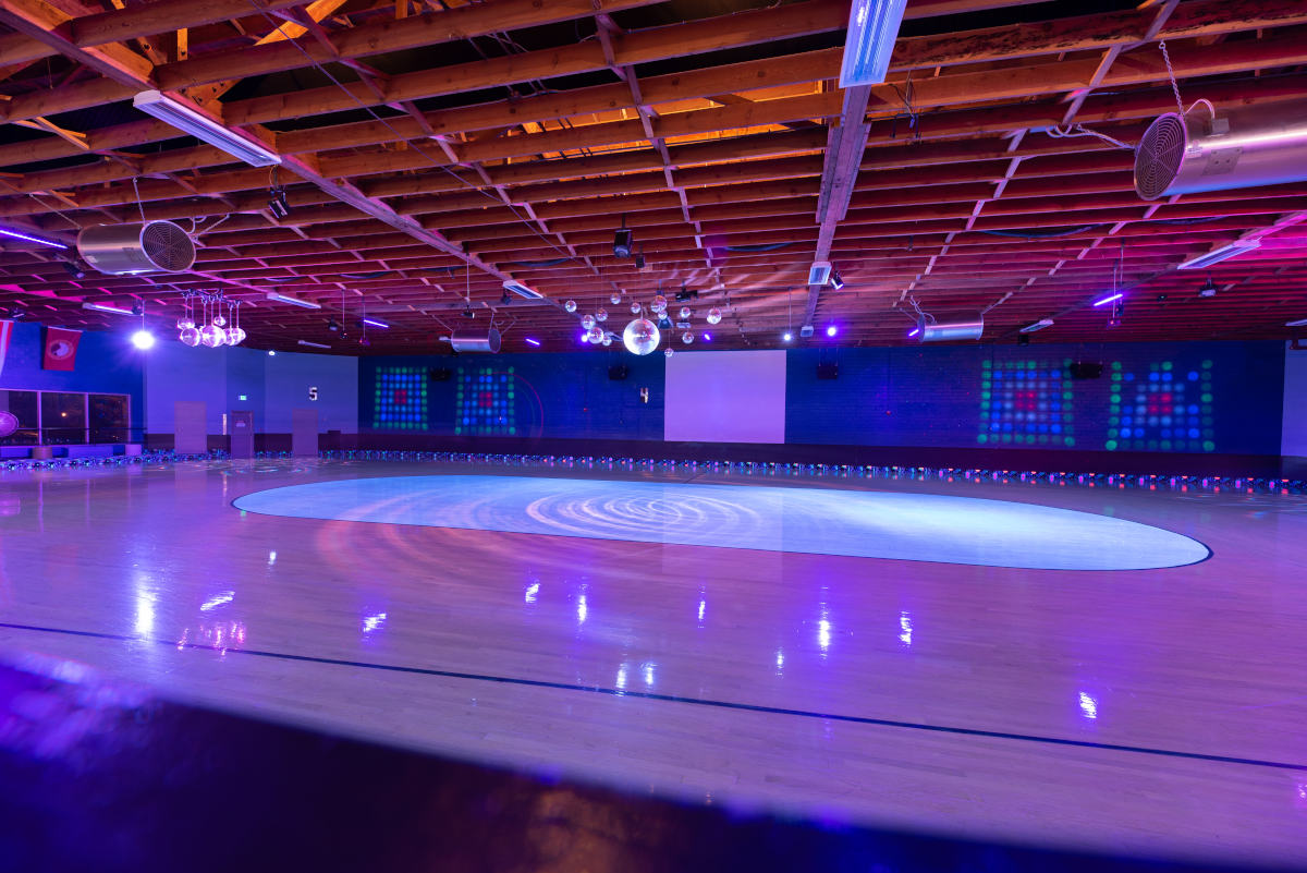 image of the the hardwood skate floor lit by blacklights with the center ring illuminated by blacklight reactive paint