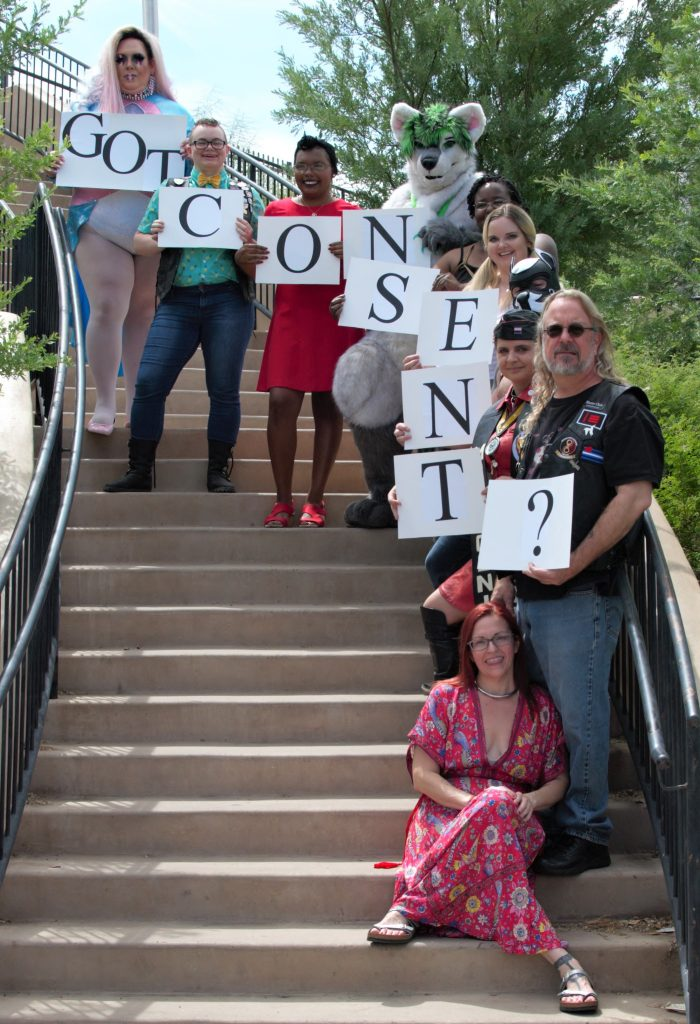 10 people holding Consent Signs on stairs