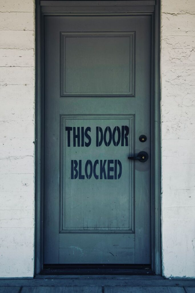 """a closed door with a sign that says """"This Door Blocked"""""""