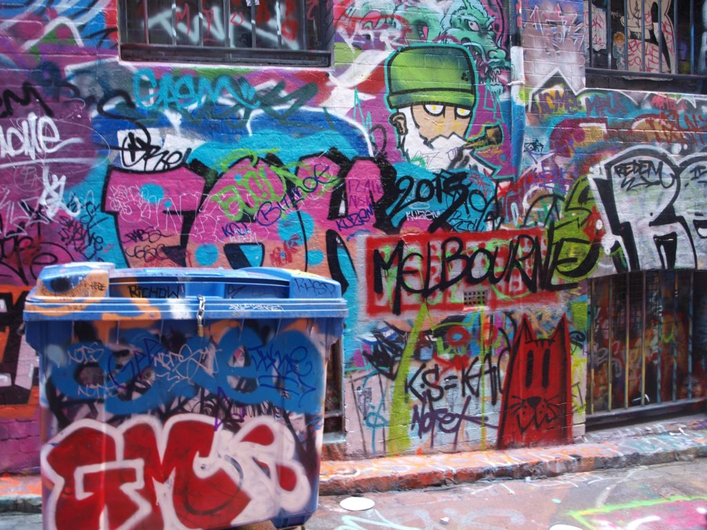 Graffiti and street art on wall and dumpster on Rutledge Lane in Melbourne