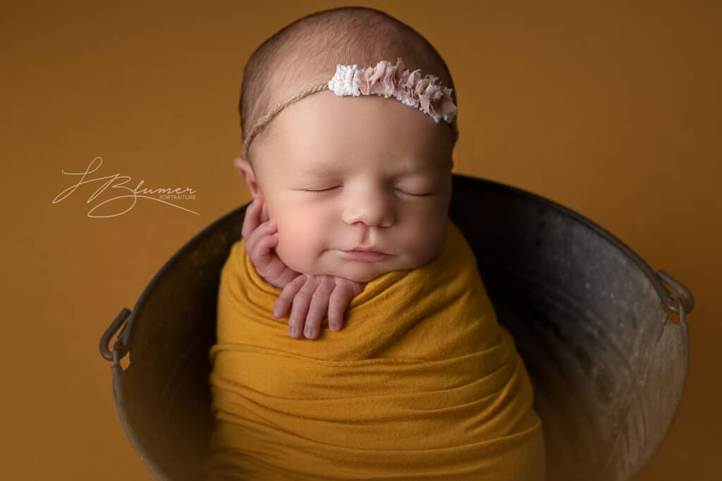 Newborn baby girl wrapped in yellow smiling in bucket