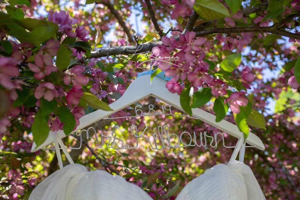Photo of bridal gown hanging in a tree with pink flowers.