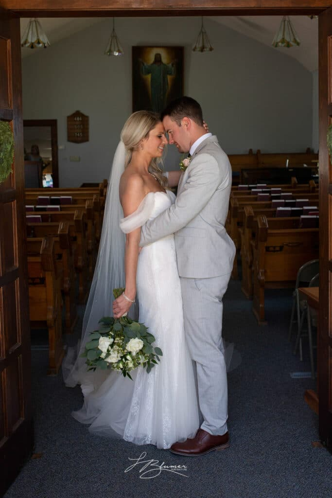 Bride and groom snuggle in the doorway of a church.