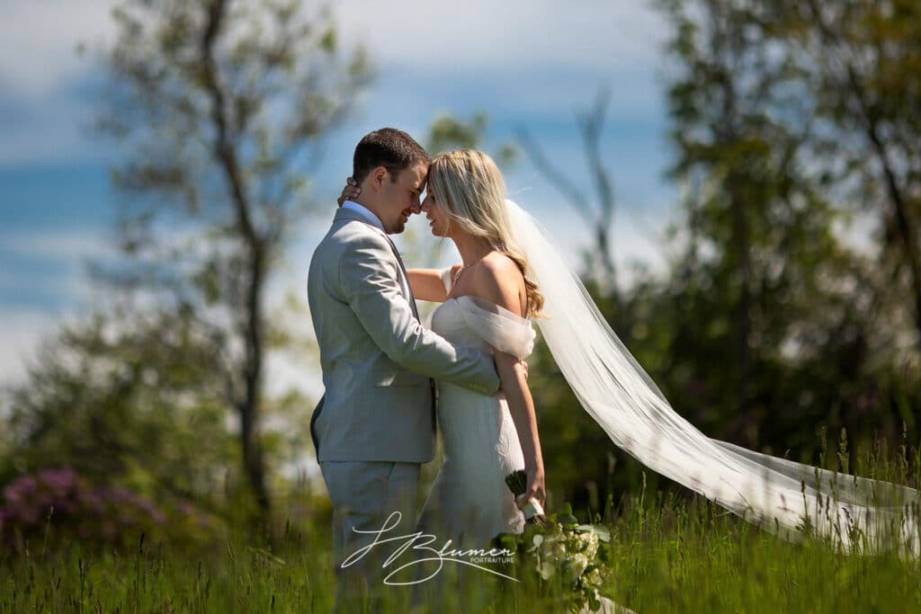 A bride and groom hold each other in a grassy field. The bride's long train flows behind her and is lit by the sun.