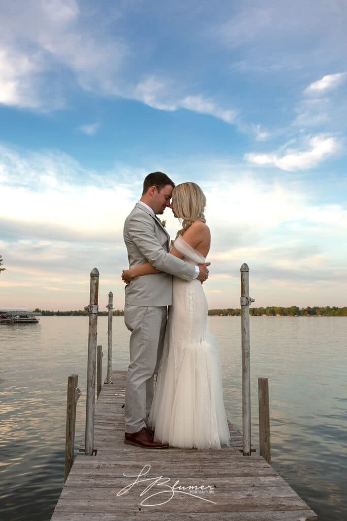 A bride and groom embrace on a wooden dock. The sky is blue and pink behind them.