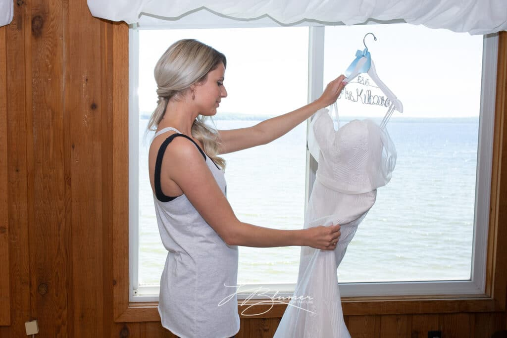 Bride gazing at her bridal gown in front of a large window.