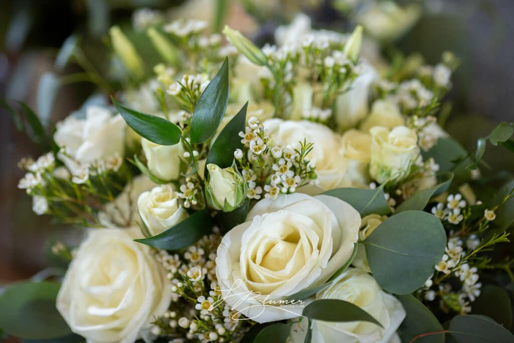 The photo depicts a bridal boquet of white flowers.
