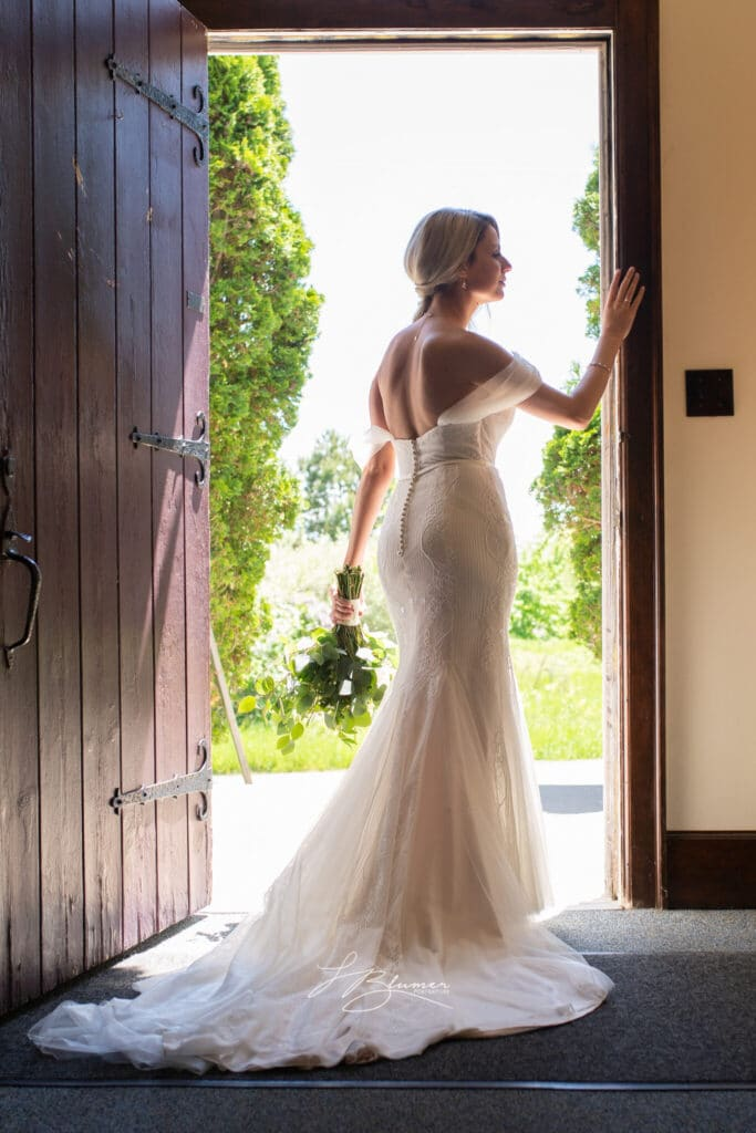 A bride stands in an open church doorway. She is lit in a silhouette.
