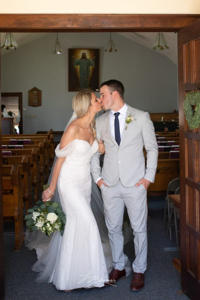 A bride and groom are holding hands and kissing in a church doorway.