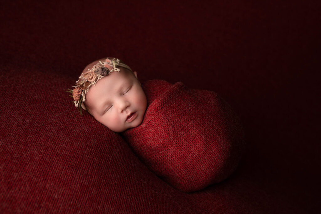 Newborn girl wrapped in red wool wearing a red floral crown.