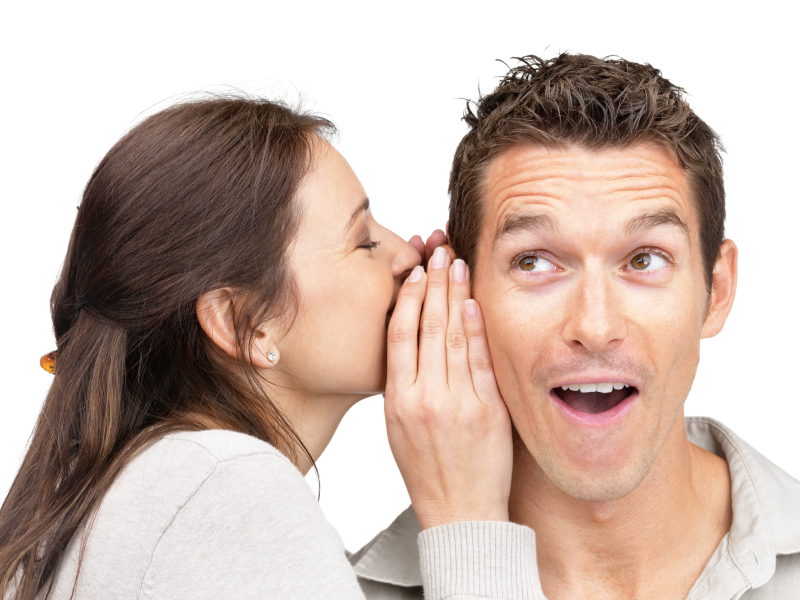 Portrait of young woman telling a secret to a man over a white background