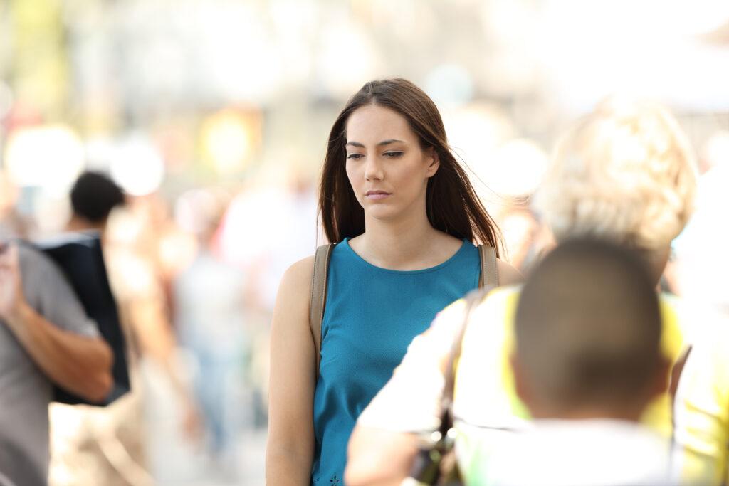 Sad woman feeling alone walking between people on the street