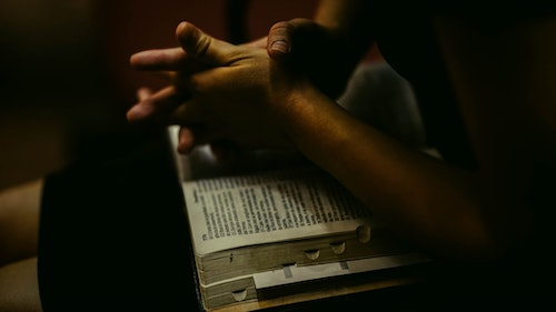hands folded on top of open bible