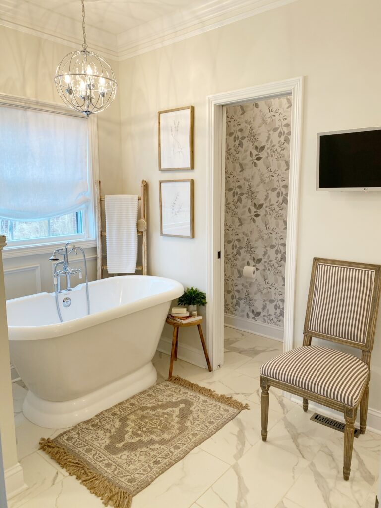 Freestanding bathtub, TV on wall and accent chair with view of new peel and stick wallpaper