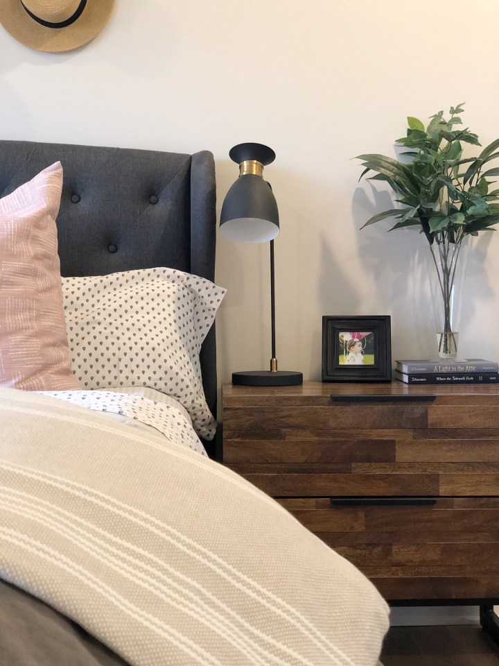 upholstered headboard in a dark gray with wood and metal nightstand.