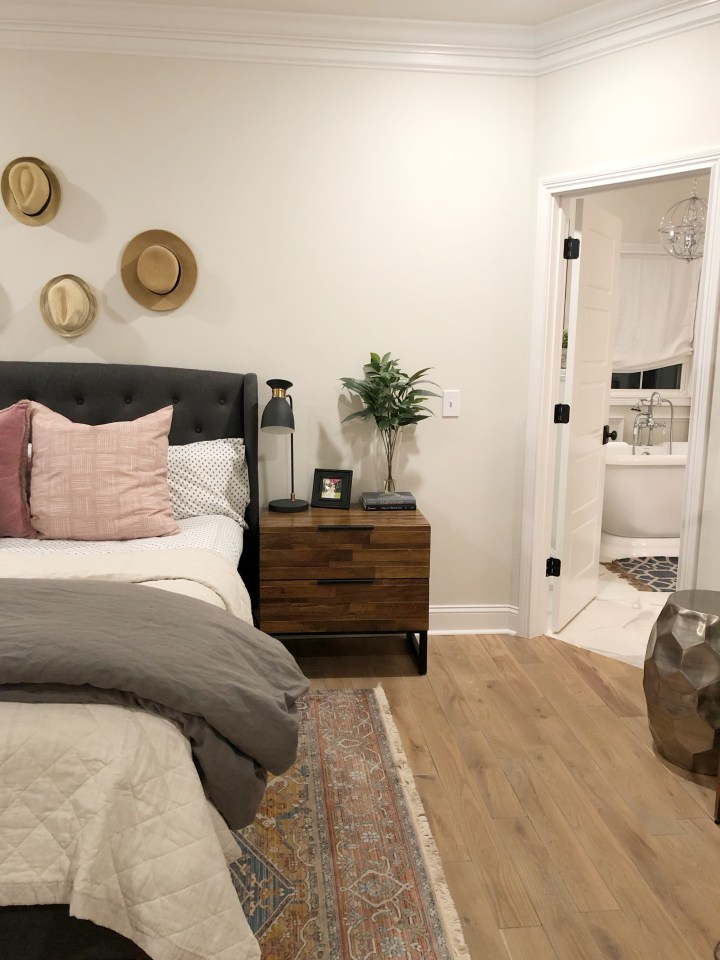 Master bedroom with area rug, nighstand and hats on the wall above the bed