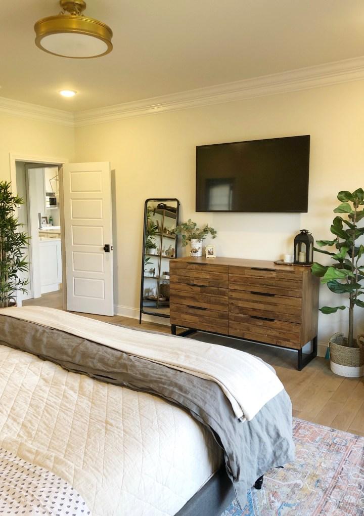 dresser in master bedroom, leaning mirror, and TV above dresser
