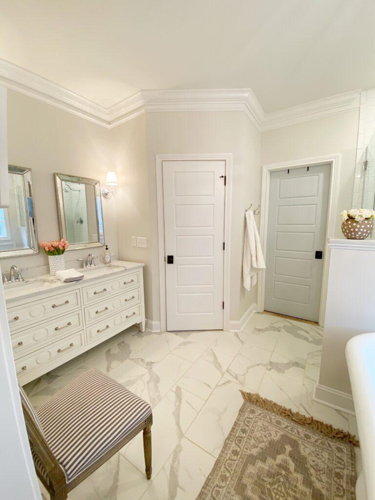 View of master bathroom including vanity, rug and closet door.