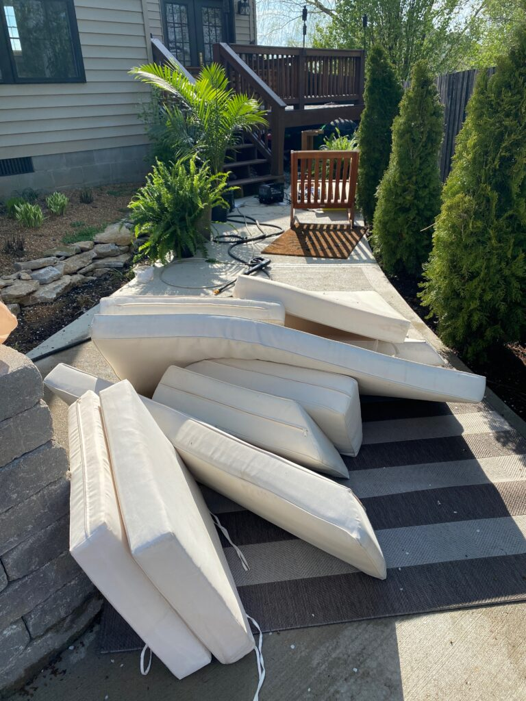 Patio cushions being power washed