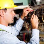 Electrician with hard-hat on fixing an electric panel