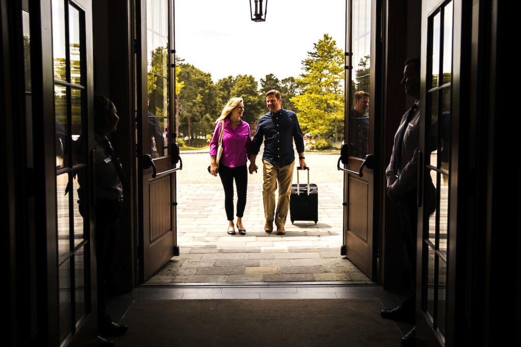 photo of man and woman with suitcase entering Mirbeau Inn & Span