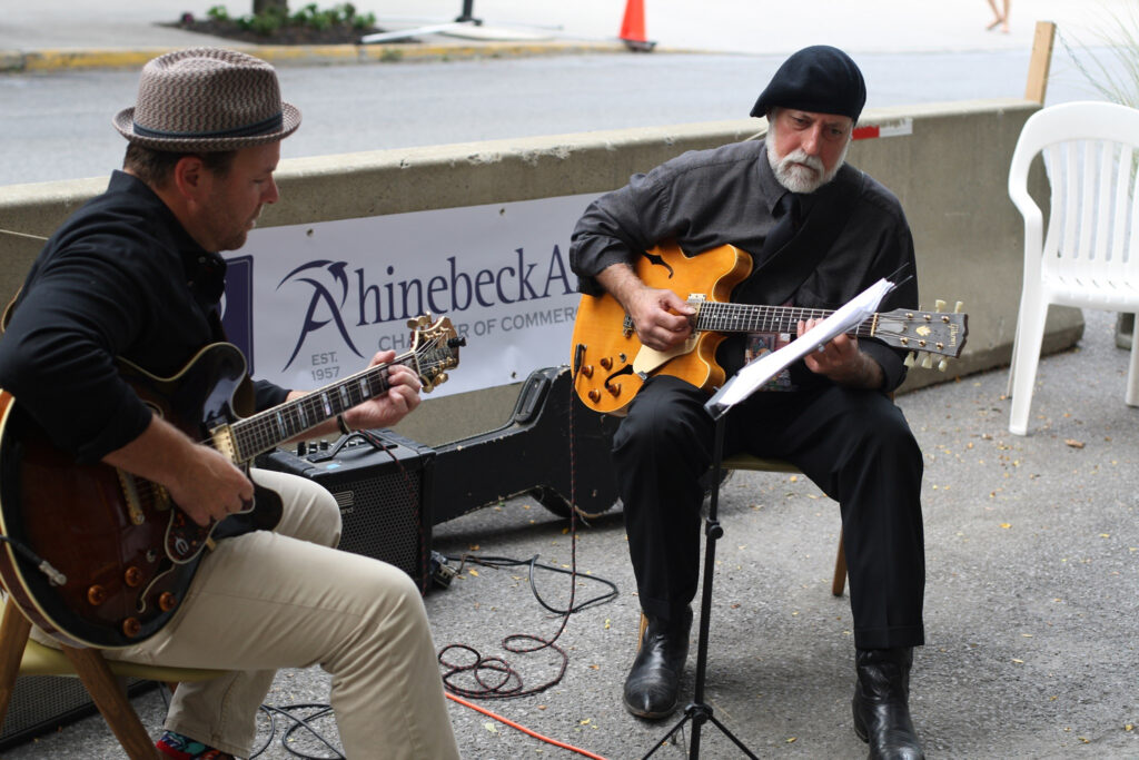 photo of 2 musicians on a bench