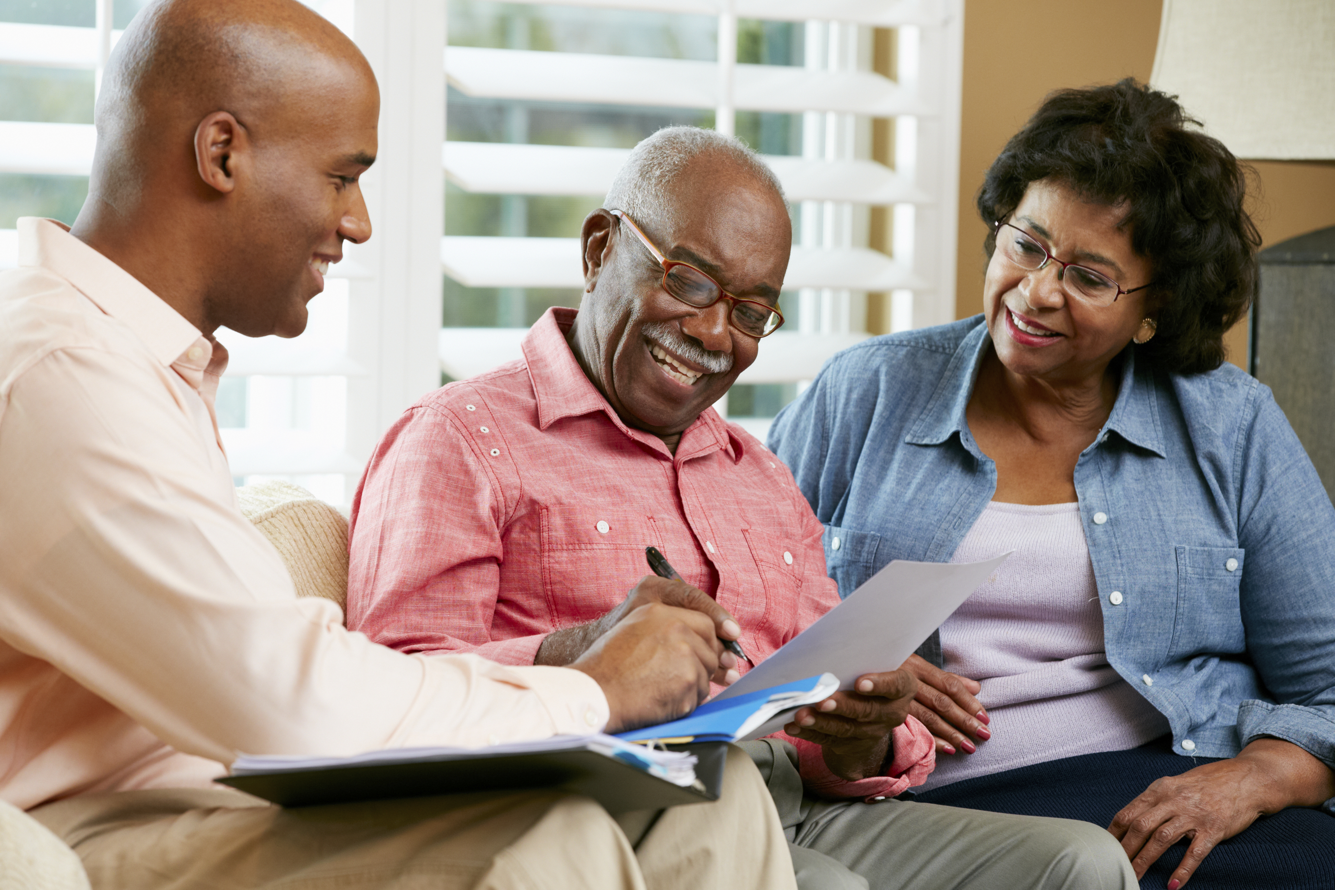 Financial Advisor Talking To Senior Couple At Home Signing Documents Smiling