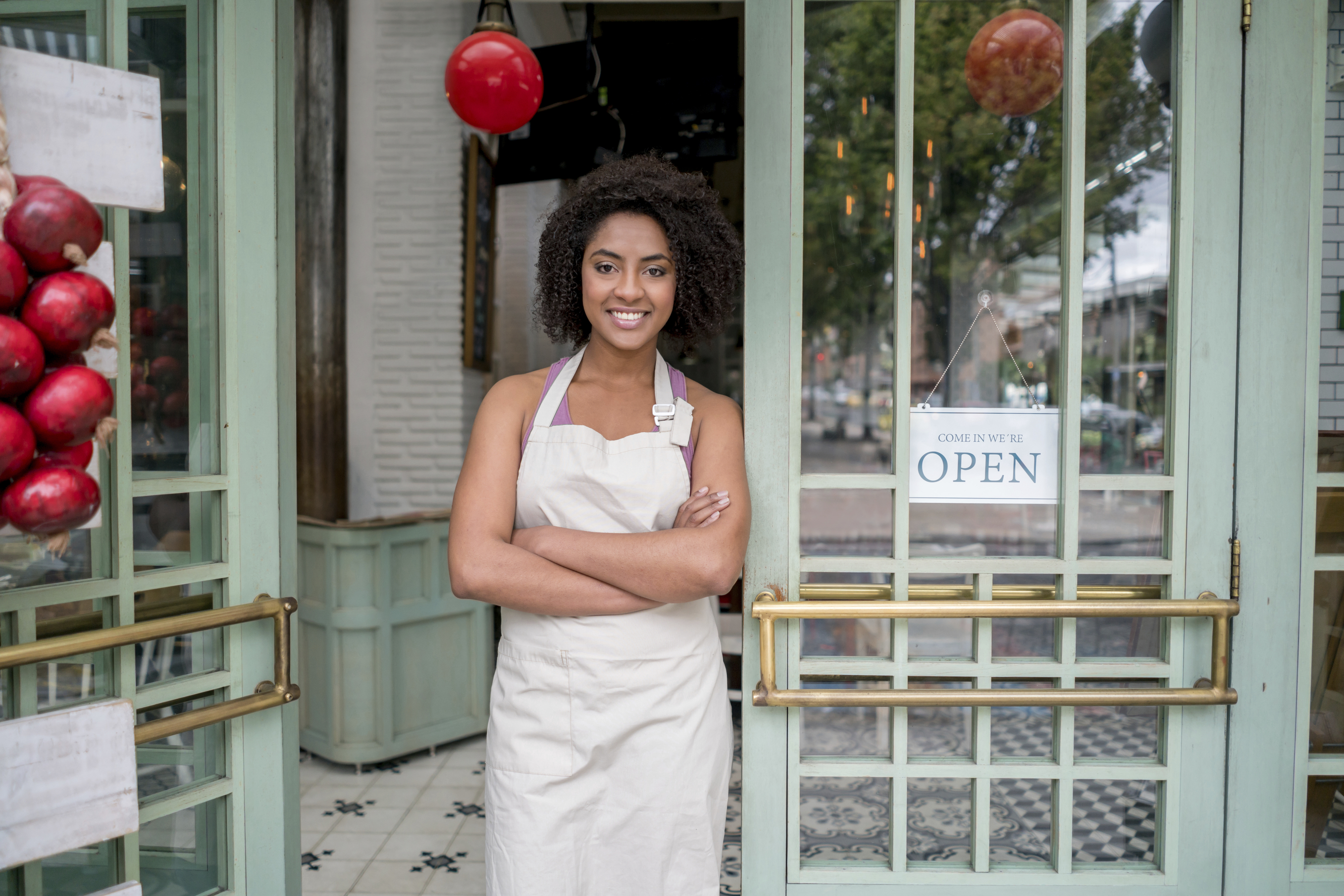 African American waitress standing at the door of a restaurant looking very happy with arms crossed