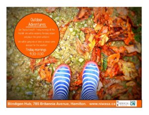 a photo of fall leaves in a variety of oranges and yellow. There is also a pair of white and blue striped rain boots.
