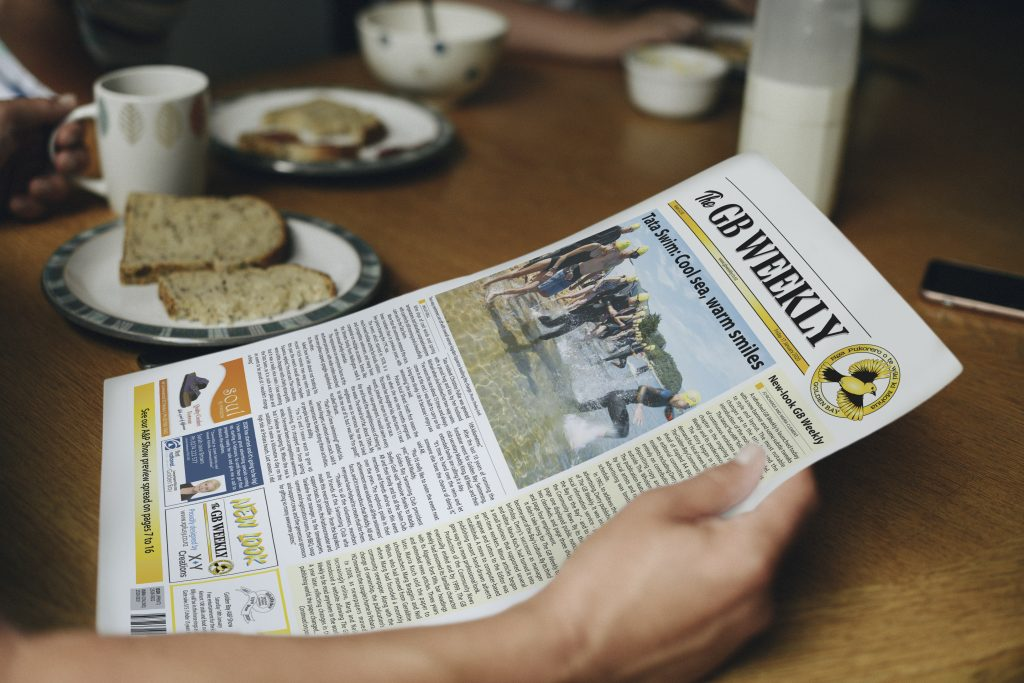 Reader at the breakfast table enjoying the new look GB weekly newspaper designed by X Plus Y Creations.