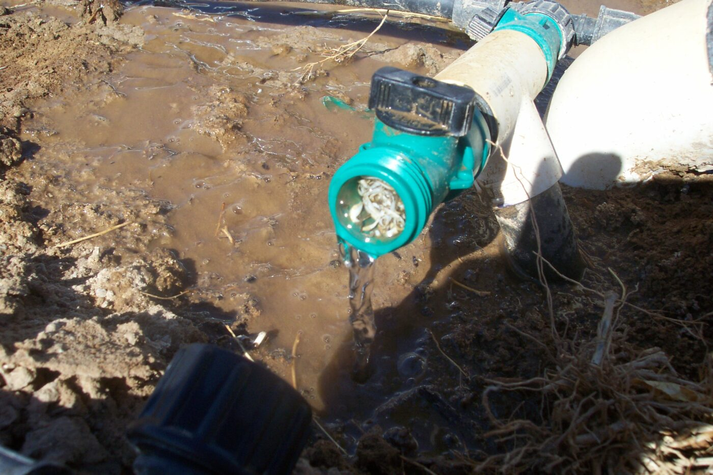 Irrigation manifold riser with plastic shavings causing pressure reduction to drip hose