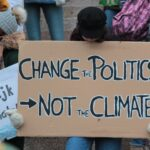 person holding change the politics not the climate printed board