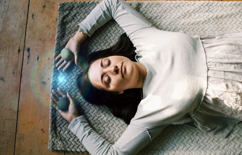 Mackensey Smith laying down and relaxing with eyes closed and arms resting over her head during a Breathwork Healing session.