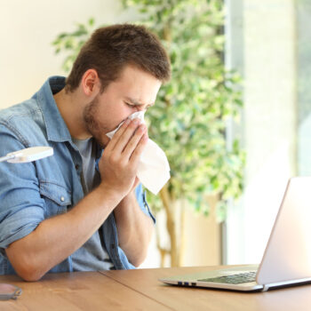Ill entrepreneur sneezing at office