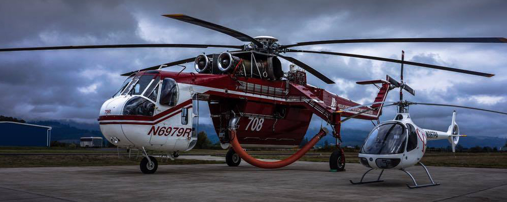 Red utility helicopter next to training helicopter at Precision Aviation
