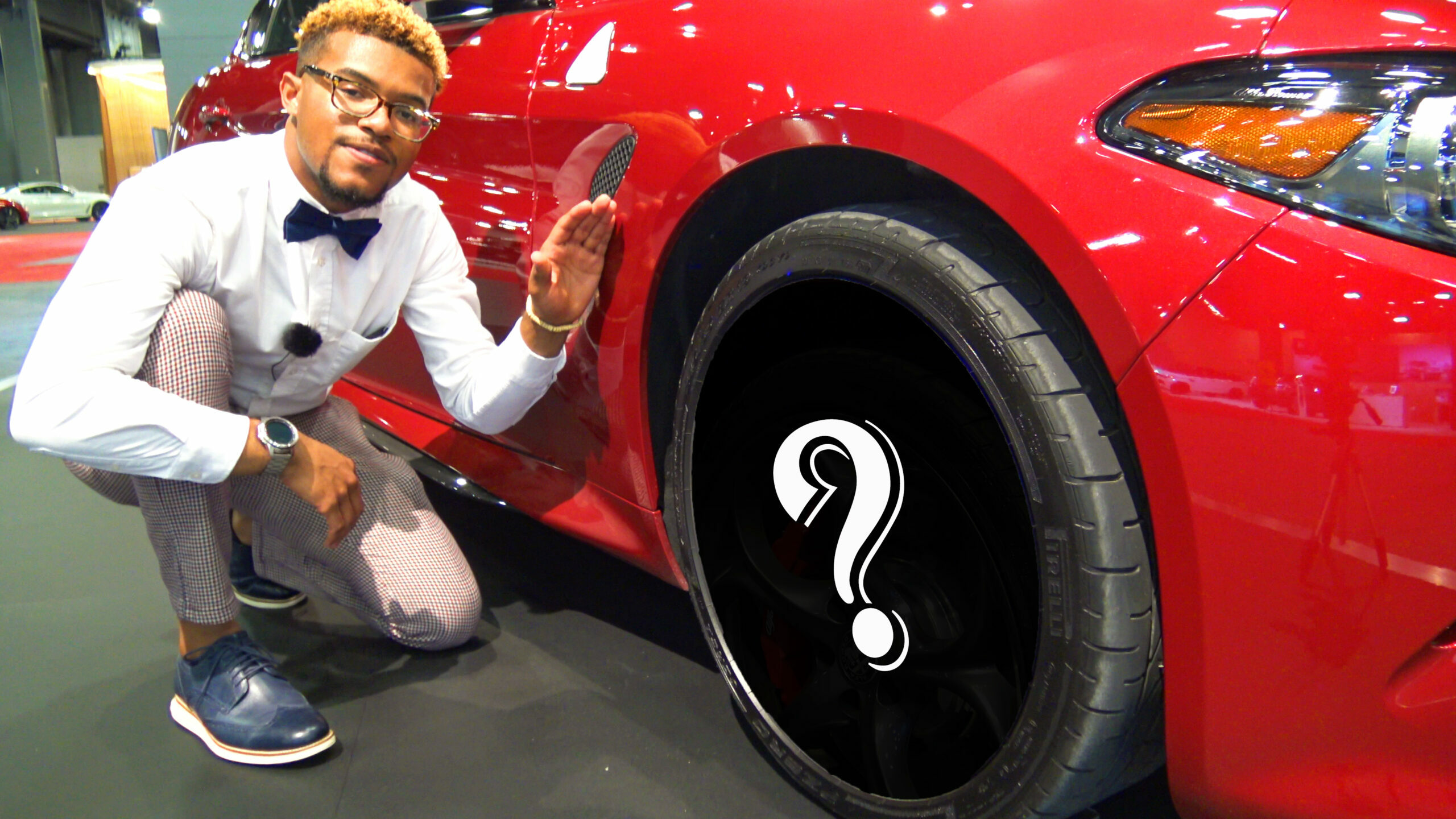 Marcus Walker next to red car (question mark covering the car's wheel/rim design).