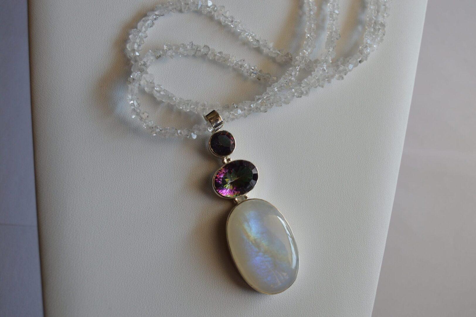 A Selene Rainbow Necklace on a surface