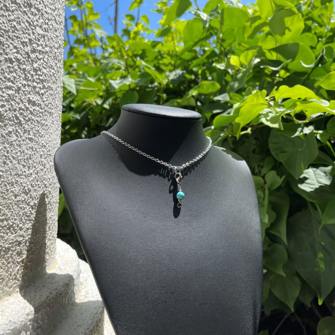 A Howlite Whisper Pendant Necklace on a bust