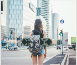 Young female with skateboard and backpack preparing to enter a crosswalk